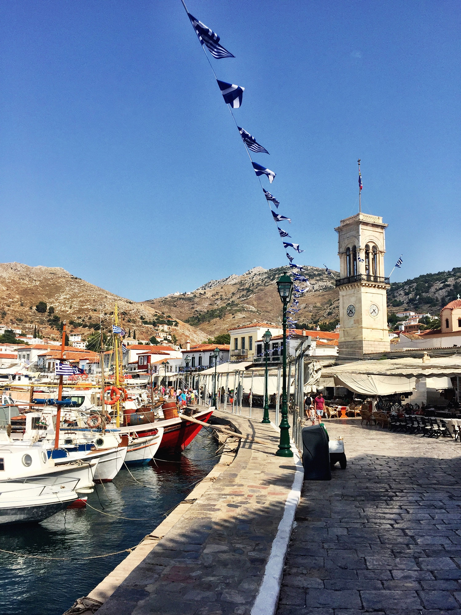 Docked boats, Greek flags and white buildings line the port