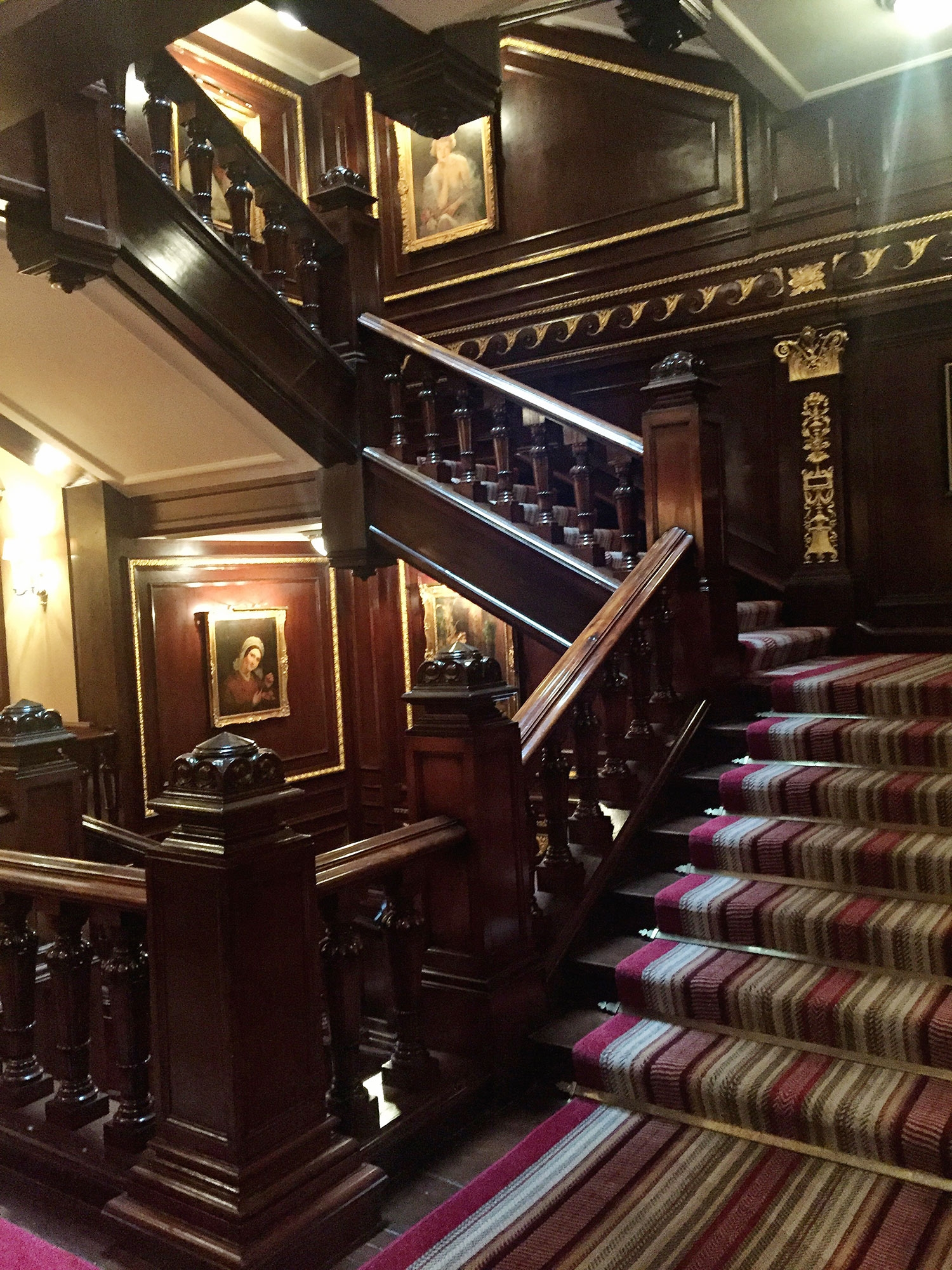 The winding staircase of The Connaught is a rich wood with a striped runner. June 2016
