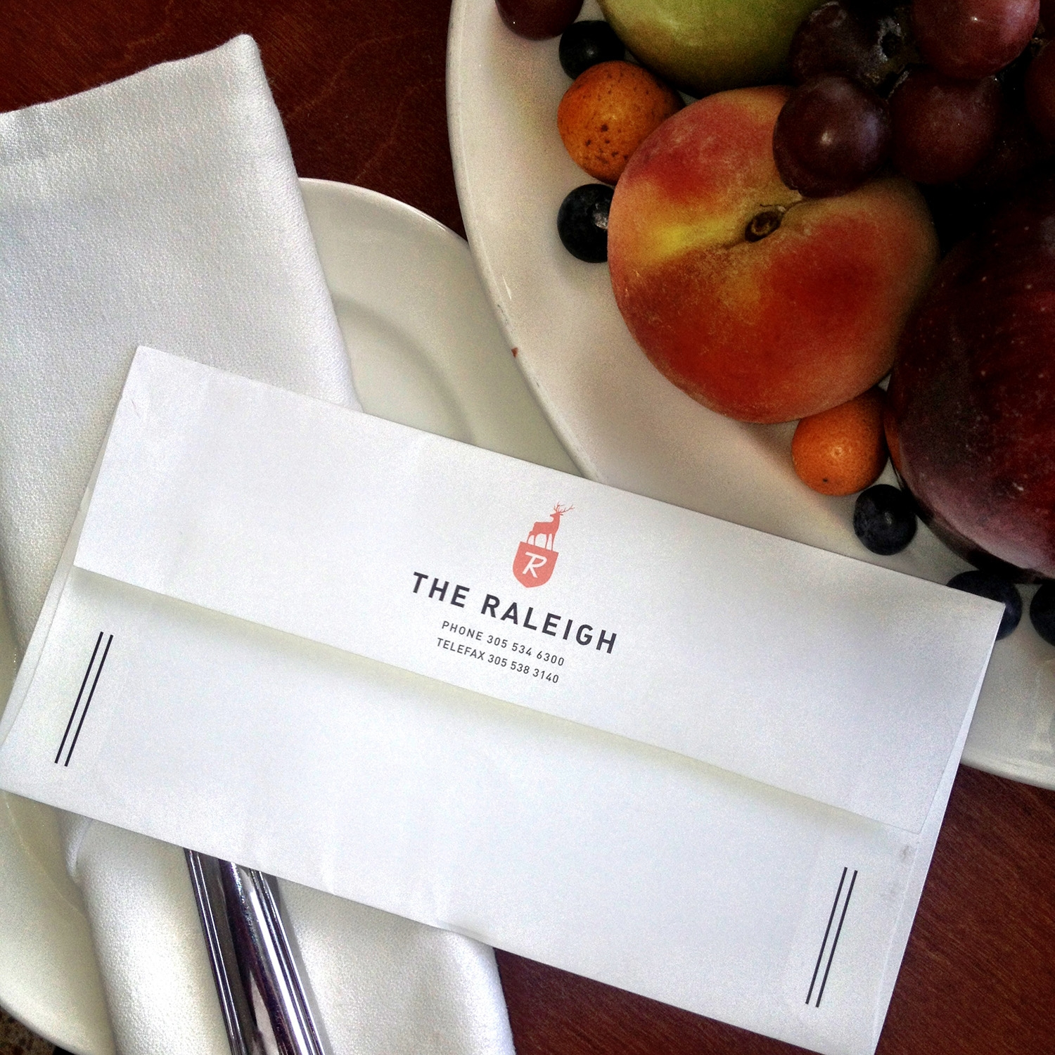 A branded 'The Raleigh' envelope sits next to a fruit bowl
