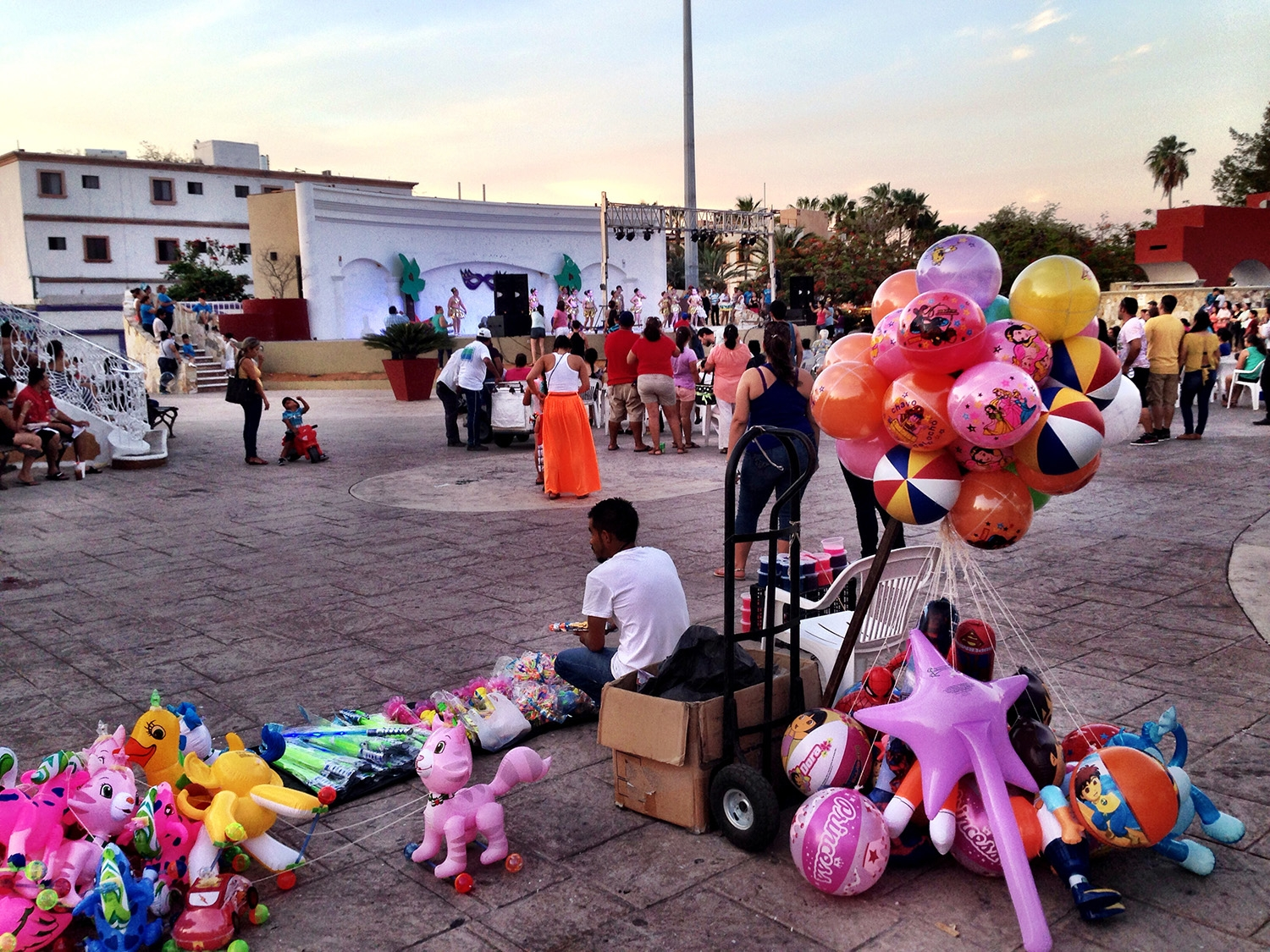 A man sits by colourful stuffed animals and balloons in the square in San Jose Del Cabo