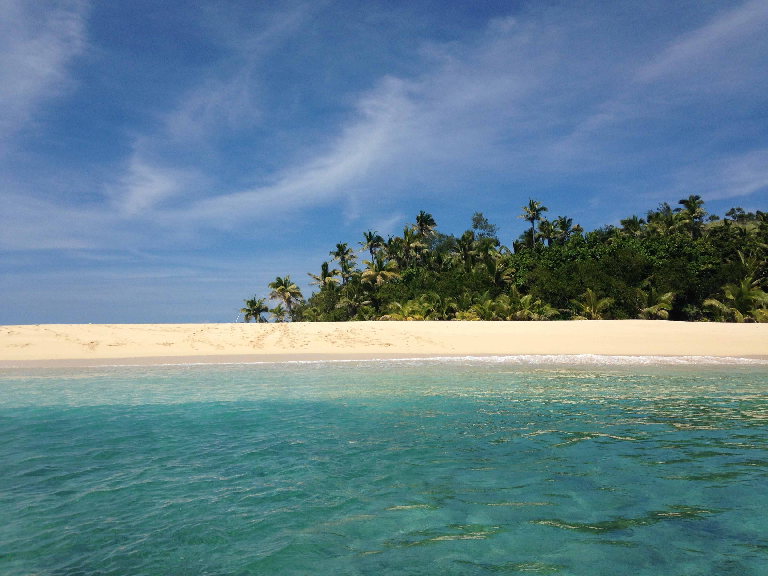 The bright white sand, blue ocean and dense shrubbery of Yasawa