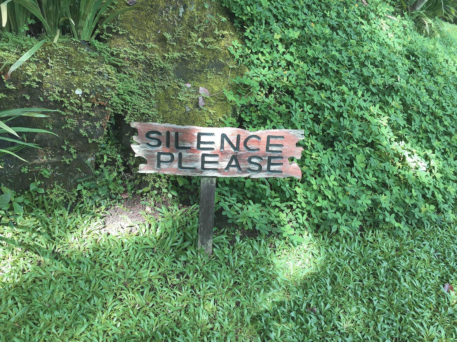 A sign in the grass that reads 'silence please'