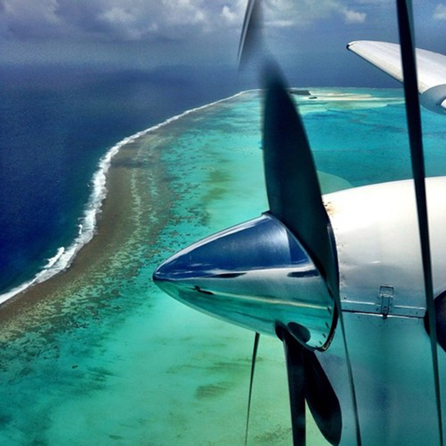 An aerial image of the Cook Island's ombre ocean and seaplane propeller