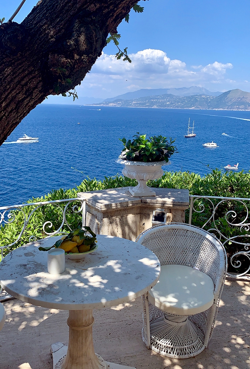 A small garden terrace with a round white table and chairs sits above the shoreline, looking down upon the boats travelling along the coast.