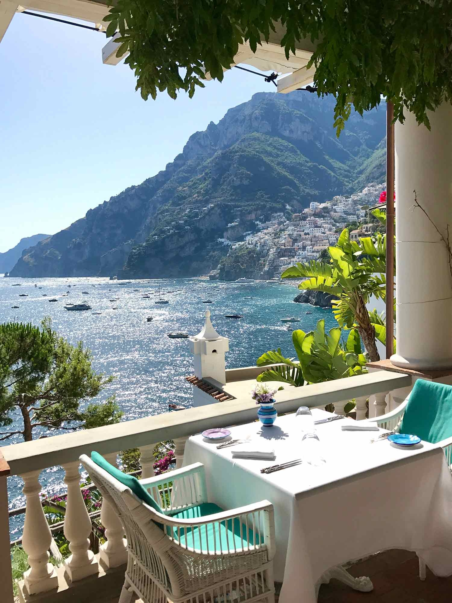 A table for two at Villa Tre Ville overlooks boats and terraced buildings on the Positano coastline