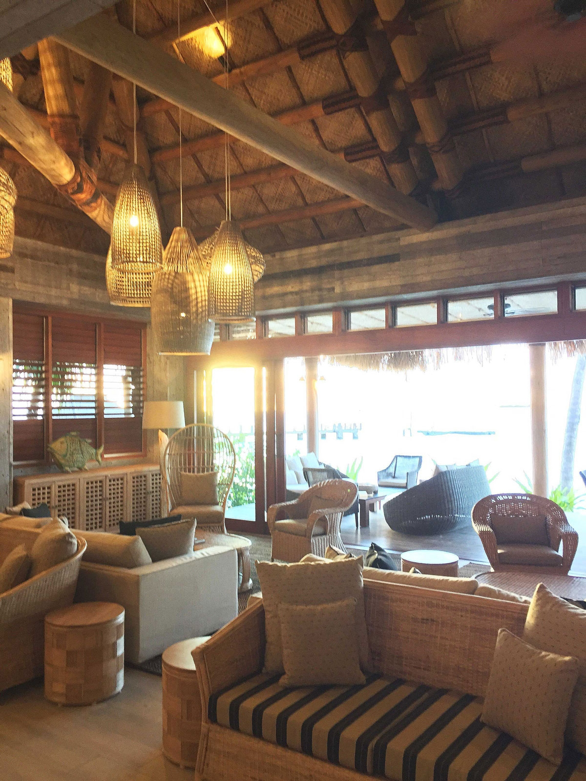 The interior of the resort bar features wicker furniture and large hanging wicker light fixtures