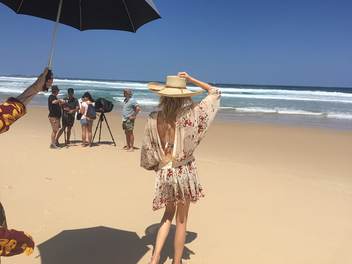 A behind the scenes shot of Lily Donaldson waiting under an umbrella while the crew chat on the beach