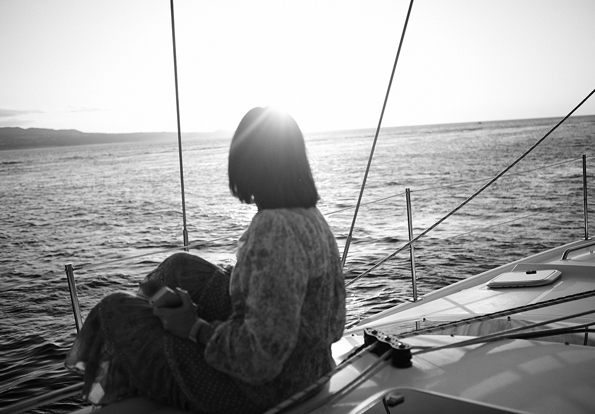 A black and white image of Nicky Zimmermann on a yacht looking out at the ocean
