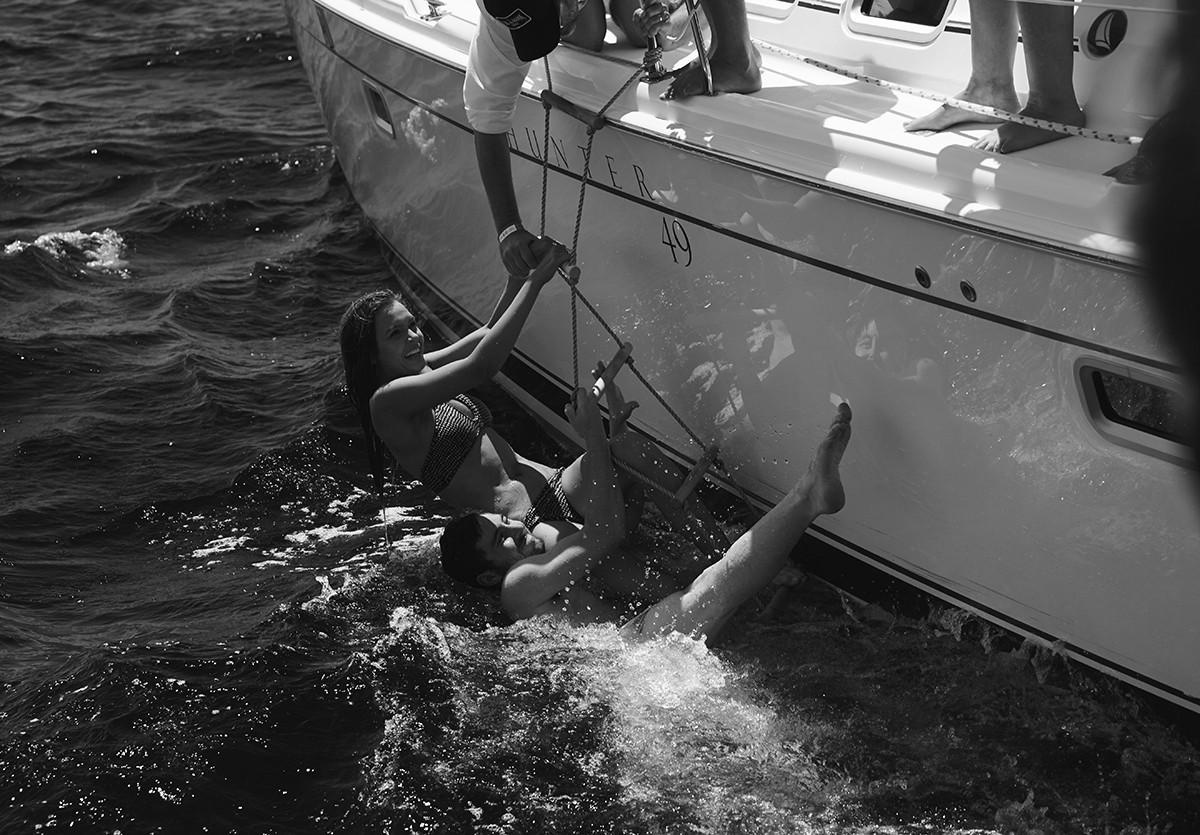 A black and white image of two girls hanging from a rope ladder in the sea on the side of the yacht