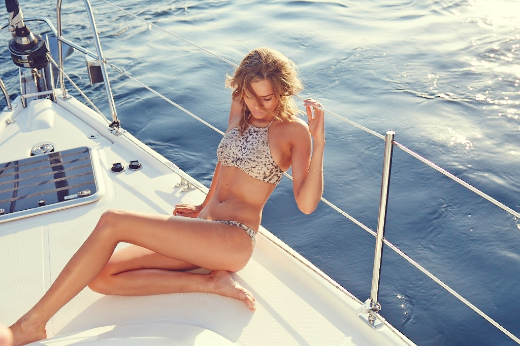 A behind the scenes shot of our model leaning against the railings of a yacht with the calm blue ocean behind her