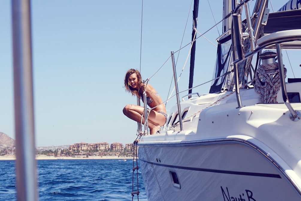 Our model sits on the side of the yacht and smiles at the camera