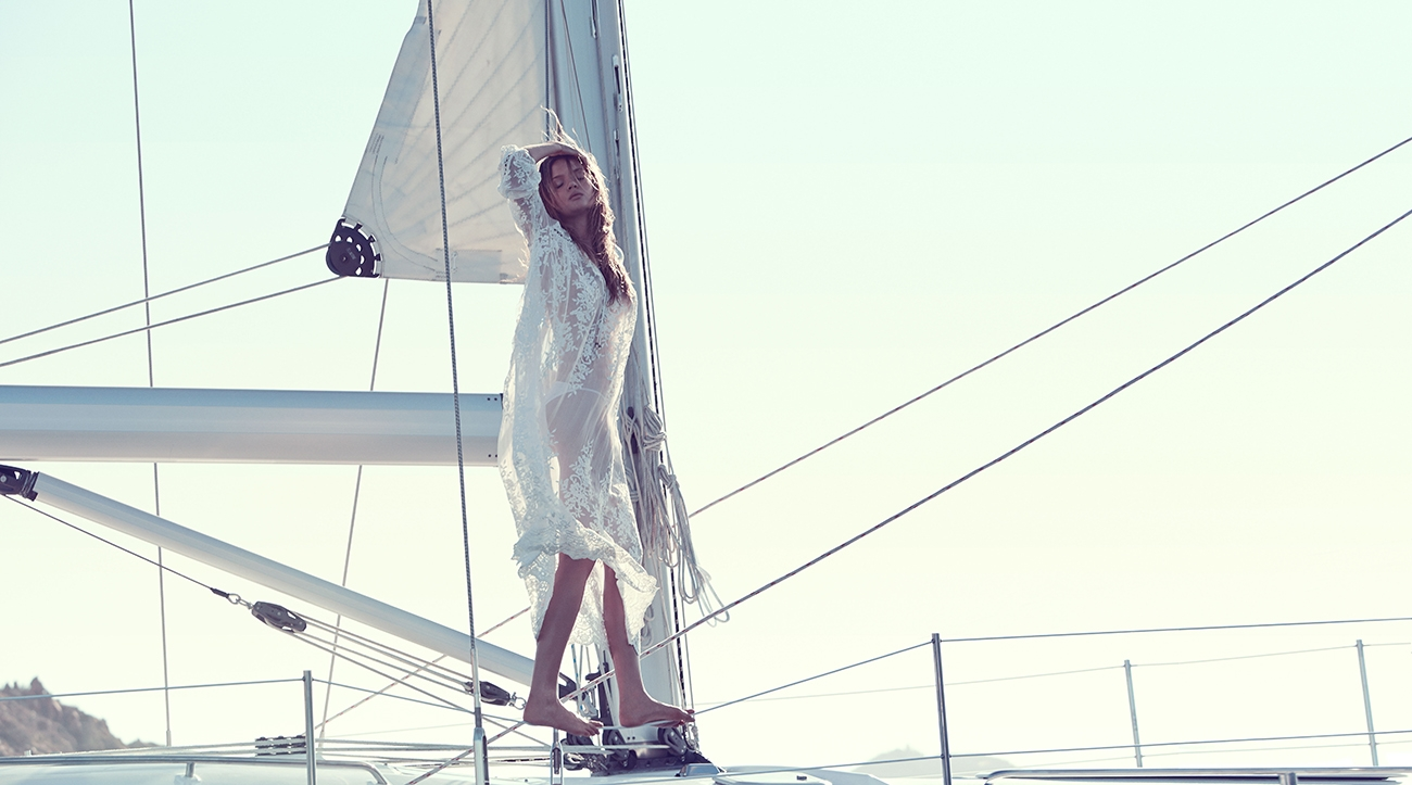 A Swim 2015 Campaign image of our model standing on the railings of a yacht with her hand on her head