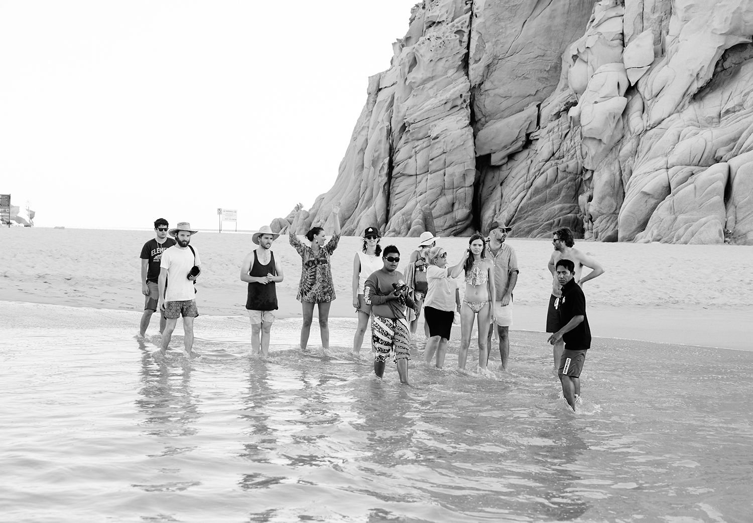 A black and white image of the crew standing along the shore on a beach in Cabo
